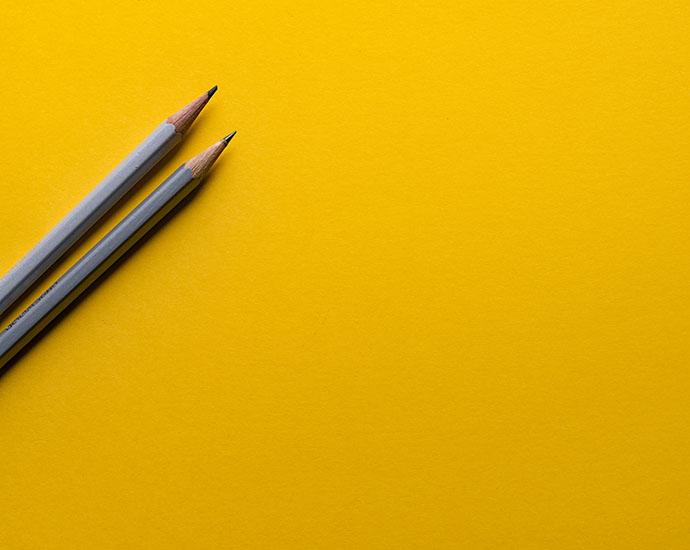Två pennor mot gul bakgrund